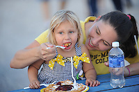 NWA Democrat-Gazette/ANDY SHUPE<br /> Gretchen Scroggin, right, feeds her 2-year-old daughter, Aynslee, a funnel cake Thursday, Sept. 3, 2015, during the Washington County Fair at the county fairgrounds in Fayetteville.
