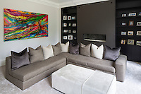 The family room decorated in tones of grey has a minimal, ordered feel. A splash of colour is provided by a vibrant piece of artwork.