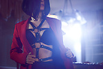 Artistic sensual portrait of a sexy young woman with short black hair taking off her red suit jacket revealing black bondage leather harness over her underwear in bright night light