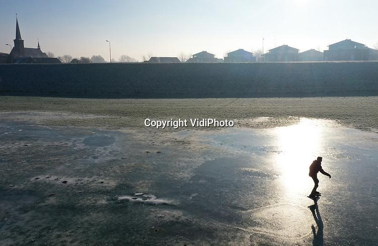 Foto: VidiPhoto<br /> <br /> HETEREN – Echte liefhebbers schaatsen op ijs wat op natuurlijke wijze ontstaat. Soms wat hobbelig en met wakken, zoals hier op de uiterwaarden bij Heteren in de Betuwe, maar dat mag de pret niet drukken. Door het hoge water is een deel van de uiterwaarden onder water komen te staan, met een boeiend ijslaagje als gevolg. De 21-jarige Daan Mulder uit Heteren greep maandag zijn vrije dag aan om het ijs op diverse plekken in de uiterwaarden uit te proberen. Gevaarlijk is het niet. Met hooguit 15 cm. water onder het ijs is het risico om een nat pak te halen vrij klein. Op diverse plaatsen in Nederland kon er vandaag op natuurijs geschaatst worden.