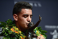 New York, NY - December 13, 2014: Hawaiian born Marcus Mariota, representing the Univeristy of Oregon, kisses the Heisman Memorial Trophy at the New York Marriott Marquis after winning the prestigious award, December 13, 2014. Mariota held a passing efficiency of 186.3, completing 254 of his 372 passes for 3,783 yards and 38 touchdowns.  (Photo by Don Baxter/Media Images International)