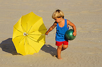 3-4 year ols boy in blue pulling a yellow umbrella over the beach sand image, photography, stock photo, picture foto, reise, photograph, image, images, photo,<br />