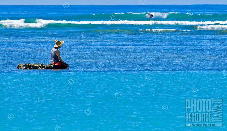 A man finds a rock outcrop in Mamala Bay to rest while fishing.  A surfer finds a nice ride in the background