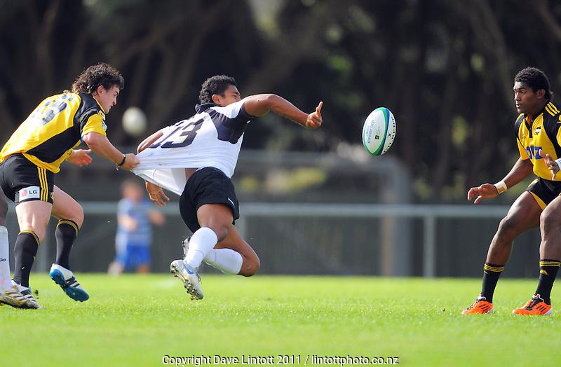 Fiji's Ravai Fatiaki passes in the tackle of Richard Buckman (left) as Waisake Naholo (right) looks on. Rugby union - Hurricanes Development XV v Fiji XV  at Trust Porirua Park, Porirua, Wellington on Friday 16 July 2010. Photo: Dave Lintott / lintottphoto.co.nz