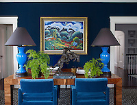 A Kim Douglas Wiggins painting hangs on the wall of Trevor's office, its walls and chairs upholstered in a cotton by Etro. The table is vintage, and the geometric patterned rug is by AM Collections
