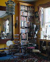 In a corner of the living room conventional books on the bookshelf jostle with others covered in fabric or wallpaper