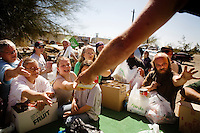 Niland, California, March, 2008 - Fighting for food and water, residents of Slab City, beg for goods provided by the traveling ministry, Church on Wheels, which delivers food and dry goods, as well as sermons, to the community every month. The service, which is a staple for many of the poorest families in the community, often devolves into a chaotic grab-fest, as residents fight for the items they need.