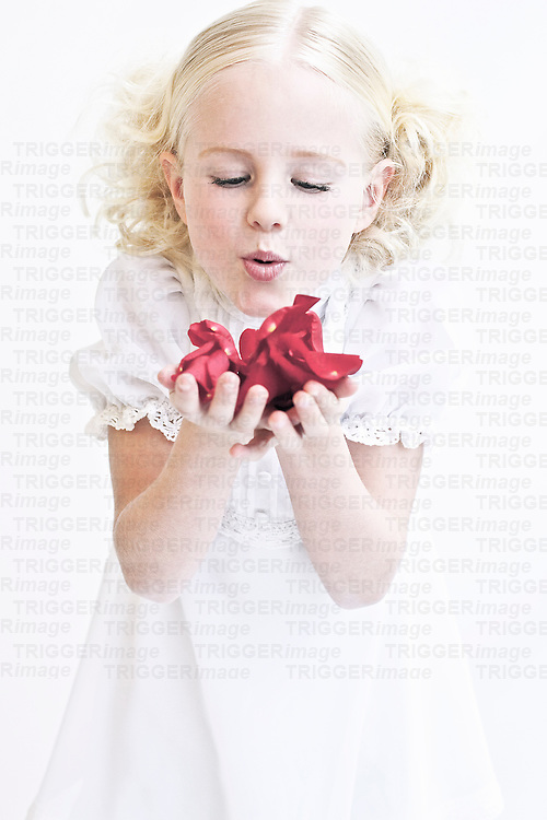 Young girl with blonde curly hair wearing white dress blowing into red rose petals