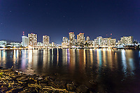 A view of buildings at night with their lights reflected on the ocean, Magic Island, Honolulu, O'ahu.