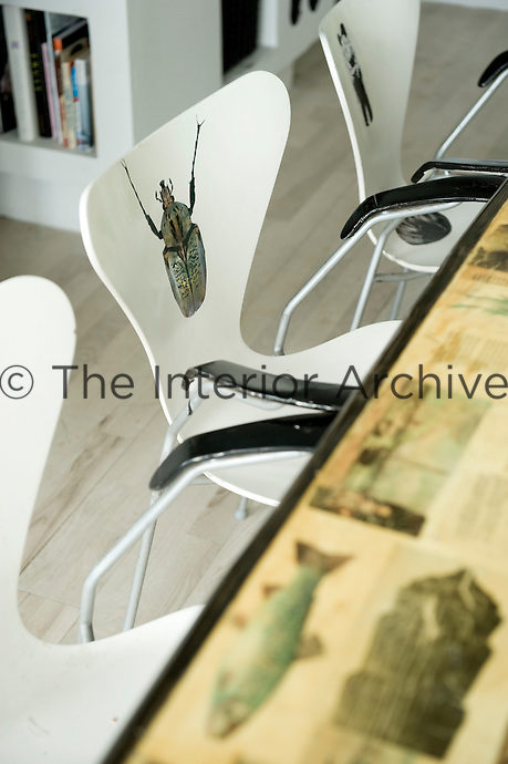 One of the Arne Jacobsen chairs which surrounds the dining table has been decorated with a beetle motif