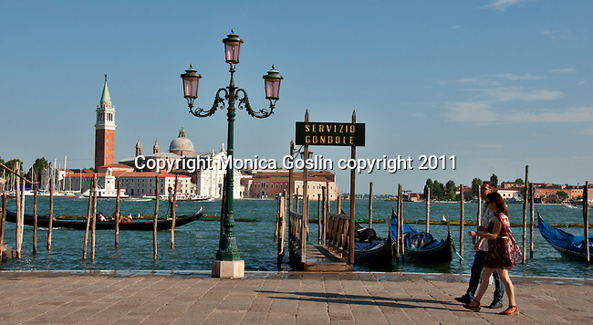 Tourists walk by a gondola stop in Venice, Italy with the Island of San Giorgi Maggiore in the background