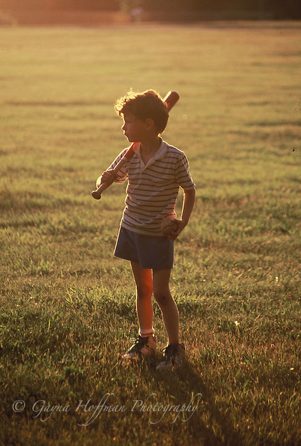 Young boy standing with bat and ball in sunset.