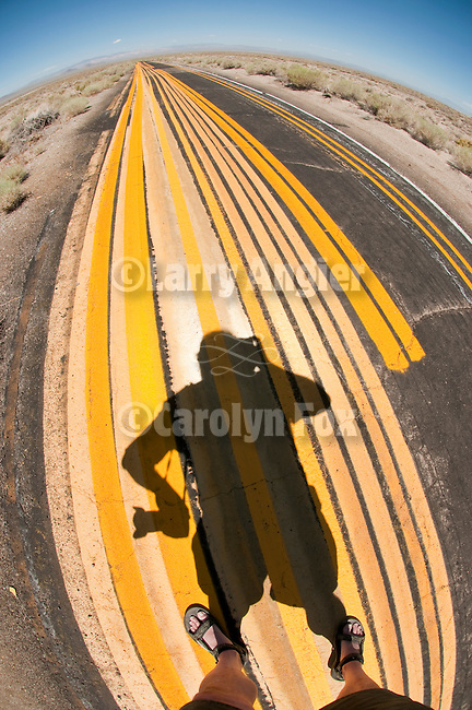 Follow the yellow brick road--my shadow on the lines. Yellow painted barrier striping used to test highway spray rig or to practice on abandoned paved roadway in central Nevada..