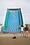 Children playing on giant inflated slide seaside attraction, Great Yarmouth, Norfolk, England parents watching using computer tablet to take photos.