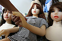 July 5, 2010 - Tokyo Japan - Ta-bo, an avid Love Doll collector, shakes hands with one of his Love Dolls, with other Love Dolls sitting on either side of it in Tokyo, Japan, on July 5, 2010. The 50-year-old Japanese engineer who rents a special three-bedroom apartment for his Love Dolls, says he owns more than one hundred, which is, to his mind, the world's largest collection of its kind.