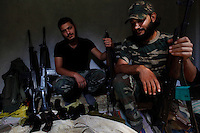 Free Syrian Army soldiers pose for a portrait along with their weapons in the Al Kassab region of northwestern Syria. Most of the weapons seen in this photograph are not in working condition. Moreover, the price of bullets is making it almost impossible for them to store enough ammunition in order to keep fighting. ..The Al Kassab region of northwestern Syria is considered the front line in the war against the Assad regime in this region of the country. This is the home to many sunni Muslims that are suffering the brunt of the shelling by the Assad army and air force - electricity was cut off months ago and basic food items along with petrol and potable water are increasingly in short supply. ..Still, the many groups that compose the Free Syria Army (FSA) in this region press on as the winter months approach. Most of the members of the FSA in this area are farmers, cell phone salesmen, clerks, carpenters, school teachers - most of them had little or no combat experience prior to joining the opposition army. Weapons and ammunition are also increasingly hard to come by as the price for bullets has skyrocketed since the conflict began 18 months ago. Rumors of an assault on this region by the Assad regime are part of everyday conversation in the villages that for the past few weeks have managed to keep the regime's army tanks and infantry out of their homes. ..© Javier Manzano