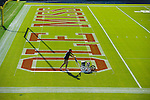 Chris Baker, associate superintendent of grounds-athletics, paints the M in Ole Miss in the north end zone ahead of Saturday's football game. Photo by Robert Jordan/Ole Miss Communications
