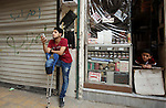 Nour, a 18-year-old Syrian man, stands in a street in a rebel-controlled area of Aleppo, on August 13, 2015. Nour lost his leg following a bomb barrel attack by forces of Syria's President Bashar al-Assad near his house in Bustan al-Qasr district. A report from the Syrian Observatory for Human Rights (SOHR) claims that over 1,000 children have been killed in airstrikes during the nation's ongoing civil war, an additional 1.5 million people have been wounded for life in the airstrikes that have been carried out by Syria's government since the Syrian conflict. Photo by Ameer al-Halbi