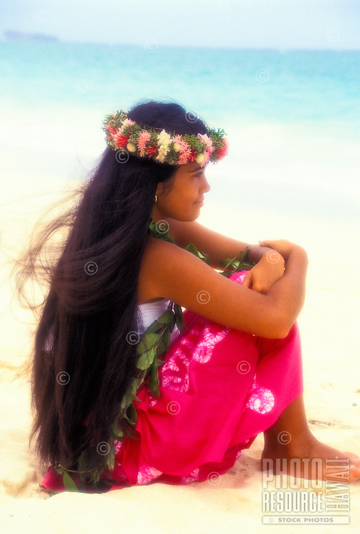 Young hula dancer with leis, sitting on beach
