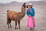 Chilean woman with a llama in the Atacama Desert near San Pedro de Atacama, Chile.