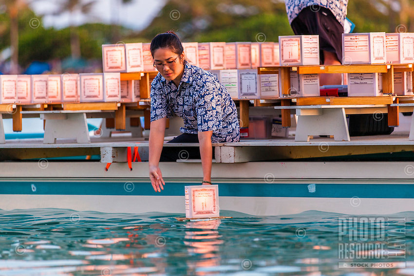 On Memorial Day, a female volunteer on a boat places a lantern in the water at the 15th Annual Lantern Floating Ceremony at Ala Moana Beach Park, Honolulu, O'ahu.