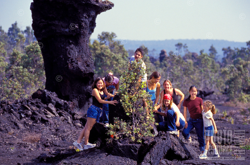 Group of local students from Punaluu at lava flow at Hawaii Volcanoes National park near an ohia tree with lehua blossoms