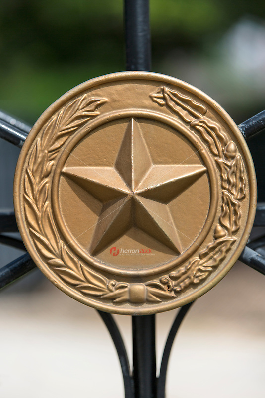 A close up of a gate at the Texas State Capitol displaying the national coat of arms of the Republic of Texas, a gold lone star encircled by a olive and live oak branches - Stock Image.