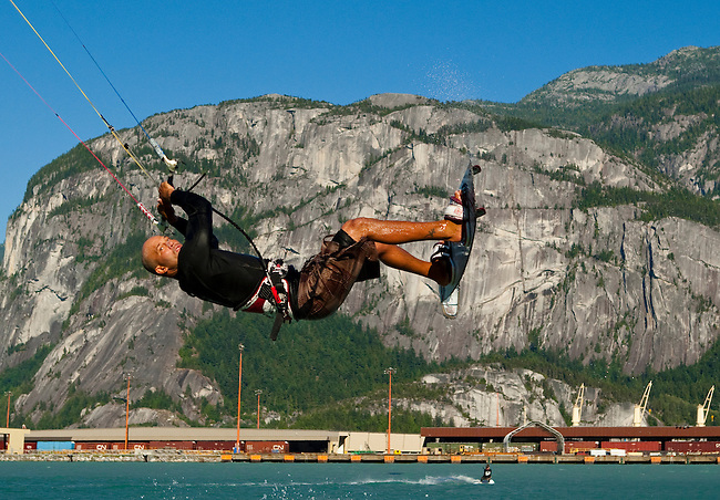 """July 21st, 2009.  Kiteboarder Colin Ernst in mid flight , with the rock formation """"the Chief"""" in the background.  The Spit in Squamish, BC.  Photo by Gus Curtis."""