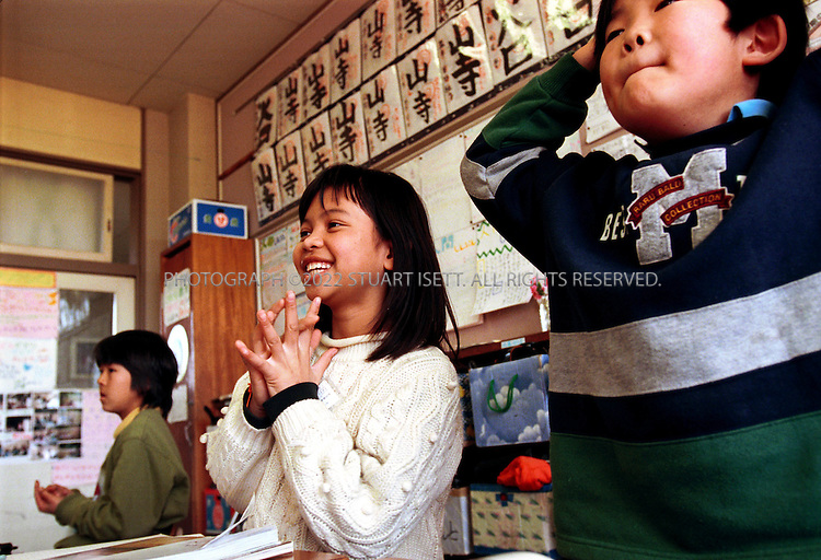 3/14/2000--Sagamihara City, Japan..9 year old Sirinthon Dwangchai (girl, center) from Laos at school at the Oshima Elementary School in Sagamihara. The city was chosen as a relocation center for some 10,000 Southeast Asia refugees. Foreign children in Japan often face discrimination and bullying in Japanese schools where many Japanese still cling to their cherished ideal of Japan as a homogenous society..All photographs ©2003 Stuart Isett.All rights reserved.This image may not be reproduced without expressed written permission from Stuart Isett.