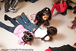 Education preschool 3-4 year olds music time group of children crawling on the floor in response to song instructions horizontal