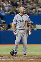 Boston Red Sox third baseman Kevin Youkilis #20 reacts to getting hit by a pitch during an American League game against the Toronto Blue Jays at Rogers Centre on June 3, 2012 in Toronto, Ontario.  (Mike Janes/Four Seam Images)