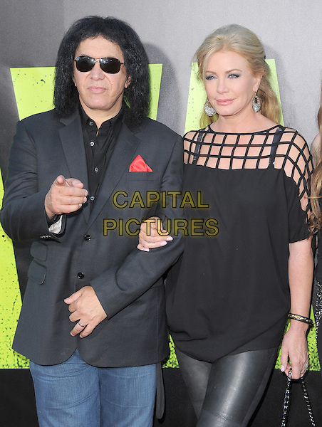Gene Simmons and Shannon Tweed.The World Premiere of 'Savages' held at The Grauman's Chinese Theatre in Hollywood, California, USA..June 25th, 2012.half length black suit jacket top sunglasses shades couple hand finger pointing .CAP/RKE/DVS.©DVS/RockinExposures/Capital Pictures.