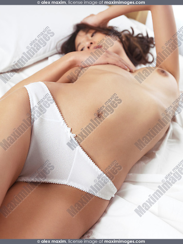 Beautiful young woman lying in bed topless in white underwear
