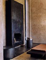 The fireplace in this living room is clad in metal and the floors are of varnished concrete