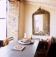 A simple table and chairs in a dining room with brick and neutral painted walls. A gilt framed mirror hangs on one wall.