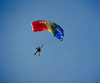 Sky diver guides colorful parachute to landing zone. Connotations - Daring, courage. sports. Cedar Valley Utah.