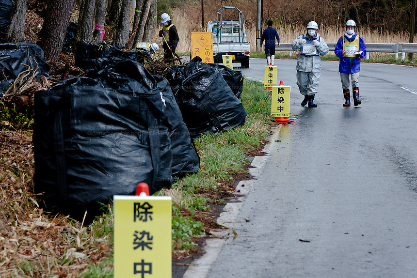 Signs warning people about decontamination chemicals being used where workmen are removing undergrowth and topsoil along a road near Katsurao in rural Fukushima, Japan, Wednesday May 1st 2013.  The Japanese government has decided to remove the topsoil and vegetation from the areas affected by radiation after the disaster at Fukushima Daichi nuclear plant on March 11th 2011