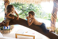 Luisa and Felix lie on a tree trunk together at the Rigoletti house. photo shoot in Zihua with Federico Rigoletti and family, Diego Garcia and his daughters, and the Wiseman family as part of the Puntarena cook book