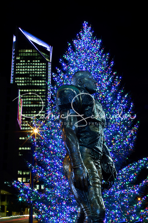 Charlotte Christmas Photography - <br /> <br /> Photography of the Carolina Panthers'  Sam Mills Statue against the backdrop of a decorated Christmas tree and the Charlotte skyline - Duke Energy Center building in uptown/downtown Charlotte, North Carolina..<br /> <br /> Charlotte Photographer - PatrickSchneiderPhoto.com