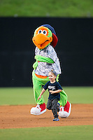 """Danville Braves mascot """"Blooper"""" races a young fan around the bases between innings of the game against the Pulaski Yankees at Legion Field on August 7, 2015 in Danville, Virginia.  The Yankees defeated the Braves 3-2. (Brian Westerholt/Four Seam Images)"""