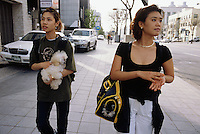 "Korea. South Korea. Seoul.  Two young teenage girls carry their pets in the streets. They are going to the dog cafe, know as  ""Fusion dog mania cafe"".  Korean people go there to eat, drink and relax themselves among hundred dogs which are there for the customers. People can love and choose among various dogs the ones they want to hold or pat.  Dogs are perceived as friendly companionship. © 2002 Didier Ruef"