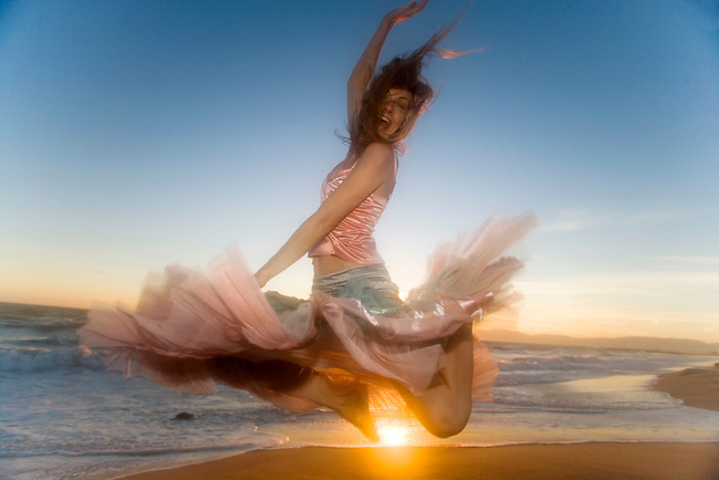 Happy girl jumps for joy at sunset at California, USA beach