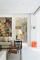 The living room has white walls and flooring and a full height window gives a view to the garden.  Neutral sofas and brown armchairs are arranged around a coffee table.