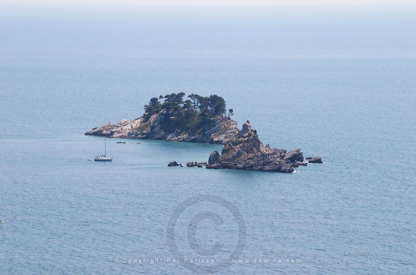A small island off the coast with a small chapel. A sailing boat moored. Near Budva and Petrovac. Montenegro, Balkan, Europe.