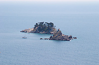 A small island off the coast with a small chapel. A sailing boat moored. Near Budva and Petrovac. Montenegro, Balkan, Europe.