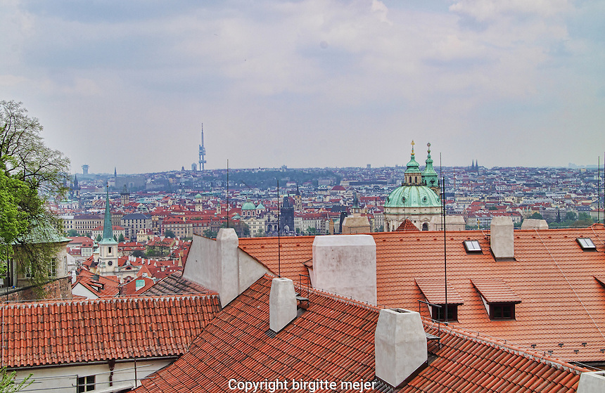 A view towards Prague's old town towards the Zizkov Tower in Prague 3, photographed from the Castle Stairs,with view to St. Nicholas Church in the center and the Zizkov tower in the far distance.<br /> In front the old red tile roofs of the Buildings leading up to the Prague Castle