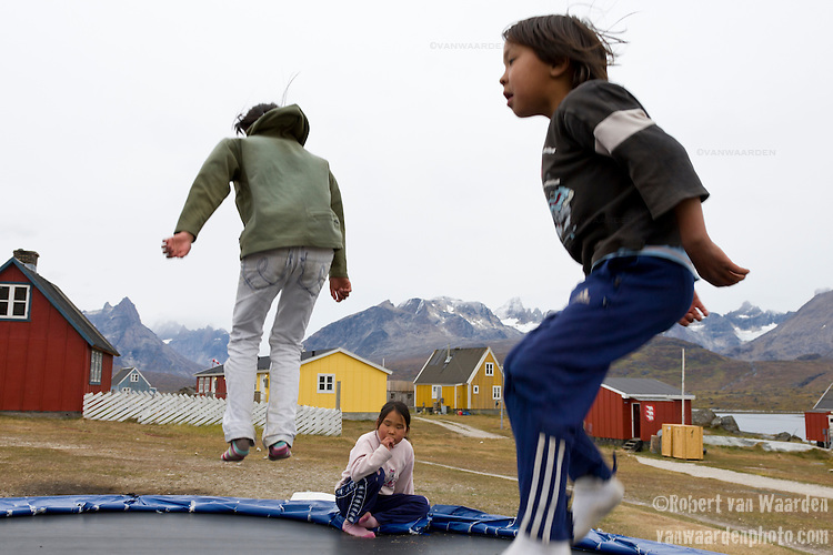 Children from the community of Tasiussaq, Greenland jump on a trampoline. In the background the landscape and mountains of Southern Greenland.
