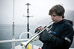 A young trumpet player plays in the rain while on an Arctic expedition. The man is part of an international Cape Farewell Youth Expedition organized by the British Council. The aim was to learn about climate change and how to communicate it through art. Here the ship sails through Prins Christian Sound in Greenland.