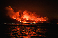 Pictured: The flames seen from the island of Evia opposite Kalamos.<br /> Re: A forest fire has been raging in the area of Kalamos, 20 miles east of Athens in Greece. There have been power cuts, country houses burned and children camps evacuated from the area.