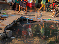 Reflection of children in the dirty water in front of their home, Tondo, slum area. Street Photography, Manila, Philippines